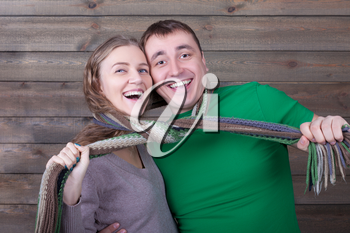 Smiling love couple wrapped in a scarf, wooden background. Funny photo shoot