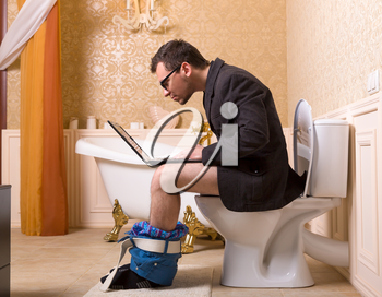 Man in glasses with laptop sitting on the toilet bowl. Luxury bathroom interior in vintage style on background
