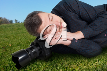 Male photographer with digital camera sleeping on a meadow