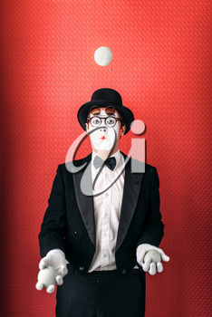 Pantomime male actor juggles with balls. Comedy mime artist in suit, gloves, glasses, make-up mask and hat. Circus juggler