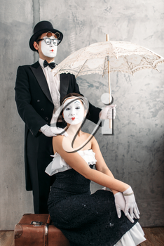Pantomime theater performers posing with vintage umbrella. Mime actors comedy performing