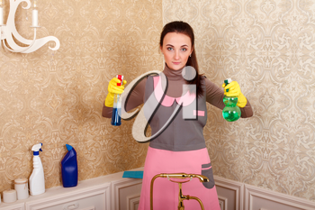 Woman in uniform and rubber gloves holding cleaning agent in hands. Housekeeping concept