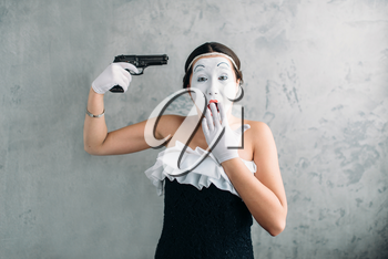 Mime female artist performing with gun. Comedian performer. Pantomime theater actress with weapon. April fools day concept