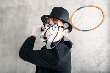 Pantomime actor performing with badminton racket. Comedy mime artist in suit, gloves, glasses, make-up mask and hat