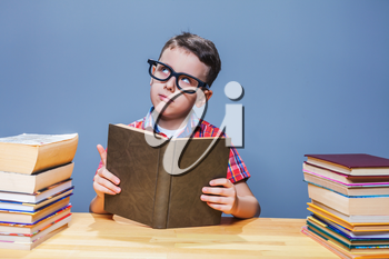 Young pupil in glasses getting knowledge from a textbook. Education concept