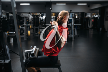 Athlete in sportswear, training on exercise machine in gym. Bearded man on workout in sport club, healthy lifestyle