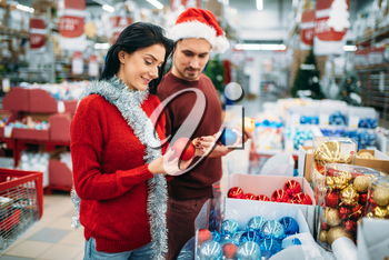 Happy couple chooses christmas tree balls in supermarket, family tradition. December shopping of holiday goods