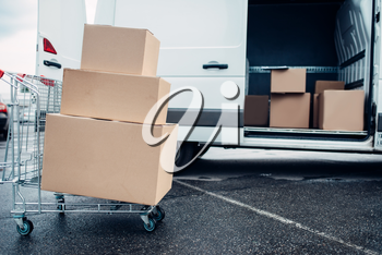 Trolley with cardboard boxes against mail van. Distribution business. Cargo delivery. Empty, clear containers. Logistic and post service