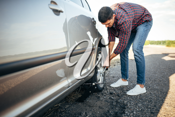 Male person hands with wheel wrench, broken car. Vehicle with puncture tire on roadside