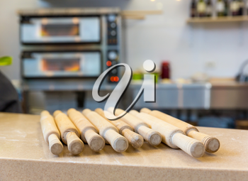Wooden rolling pin on the table closeup. Equipment for making pizza