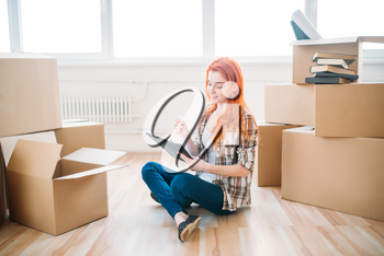 Young woman with notebook sitting on the floor among cardboard boxes, housewarming. Relocation to new home