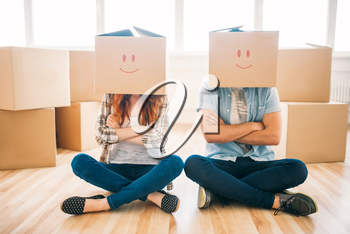 Playful couple with cardboard boxes on their heads sitting on the floor, moving to new home, housewarming. Man and woman have a fun