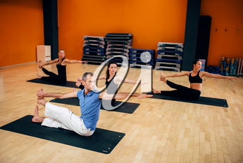 Yoga training, female group workout with male trainer in gym. Yogi exercise indoor