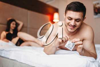 Love couple lying in bed, smiling man holds a condom in his hand. Intimate life, sex lovers in bedroom