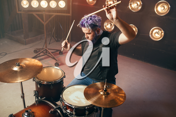 Bearded drummer with colorful hair on the stage with lights, vintage style. Musical performer, live music performing