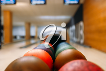 Color bowling balls in feeder, lane with pins on background, nobody. Bowling game concept