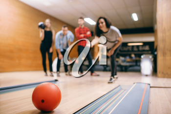 Female bowler throws ball on lane, strike shot. Bowling alley teams playing the game in club, active leisure