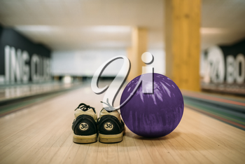 Bowling ball and house shoes on lane in club, closeup view, nobody. Bowl game concept, active hobby