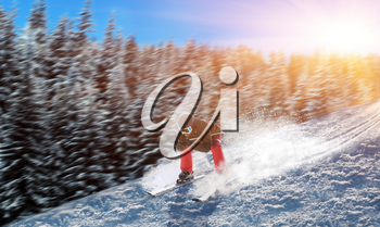 Skier in helmet and glasses racing from the mountain. Winter active sport, extreme lifestyle. Downhill skiing