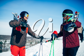 Male and female skiers poses with skis and poles in hands, blue sky and snowy mountains on background. Winter active sport, extreme lifestyle. Downhill skiing