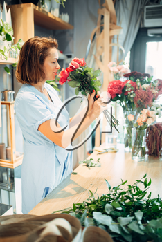 Female florist holds fresh red roses flower shop. Floristry business, bouquet making
