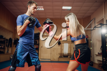 Female kickboxer in gloves practicing hand punch with male personal trainer in pads, workout in gym. Woman boxer on training, kickboxing practice