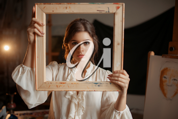 Female painter holds wooden frame at her face in studio, portrait drawing concept. Artist painting in class, workshop interior on background
