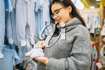 Happy future mother buys childrens clothes in the store for newborns. Pregnant woman in shop of goods for infants