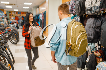 Couple choosing backpacks for travelling, shopping in sports shop. Summer season extreme lifestyle, active leisure store, customers buying tourist equipment