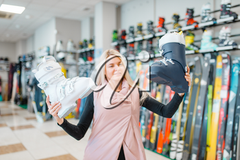 Woman shows white ski or snowboarding boots in sports shop. Winter season extreme lifestyle, active leisure, female customer with equipment