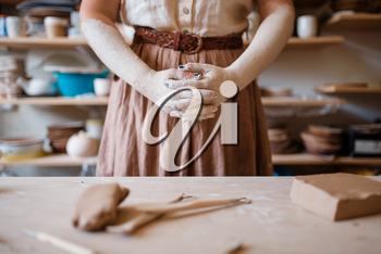 Female artisan hands covered with dried clay, pottery workshop interior on background. Woman molding a bowl. Handmade ceramic art, tableware making