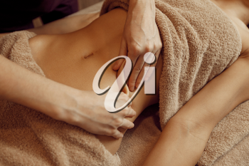 Female masseur pampering the stomach to young woman in towel, professional massage. Massaging and relaxation, body and skin care. Attractive lady in the spa salon
