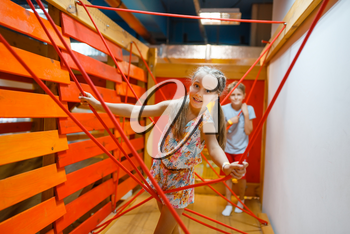 Two little girls playing in rope labyrinth, playground in entertainment center. Play area indoors, playroom