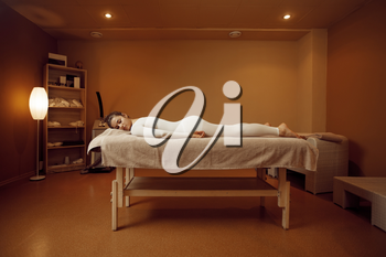 Young woman in massage suit relaxing on the table. Massaging and relaxation, body and skin care. Female person lying down in spa salon