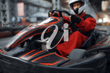 Kart racer enters the turn, karting auto sport indoor. Speed race on close go-cart track with tire barrier. Fast vehicle competition, high adrenaline leisure