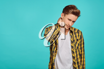 Young tired man portrait, blue background, emotion. Face expression, male person looking on camera in studio, emotional concept, positive feelings