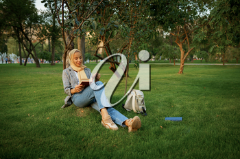 Arab female student in hijab reading textbook in summer park. Muslim woman with books resting on the lawn. Religion and education