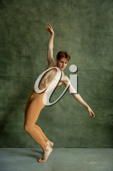 Male ballet dancer poses at grunge wall in dancing studio. Performer with muscular body, grace and elegance of dance