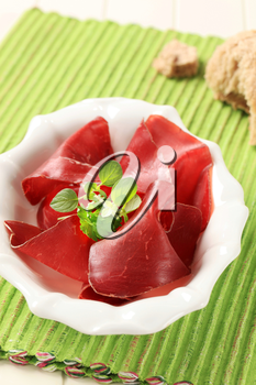Thin slices of dried meat in a bowl