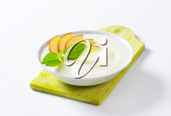 Bowl of smooth milk pudding with apple slices