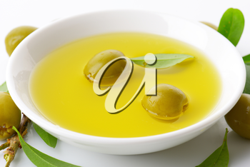 Pitted green olives and bowl of oil