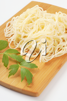 cooked thin noodles on cutting board