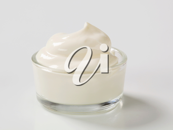Swirl of smooth white cream in a small glass bowl
