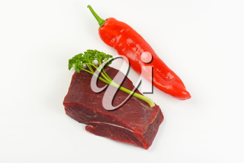 raw beef rump, fresh parsley and red pepper on white background