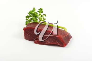 raw beef meat and fresh parsley on white background
