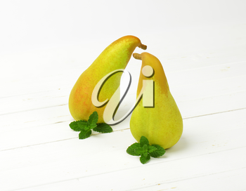 two yellow pears on white wooden background