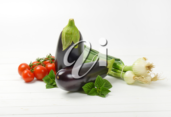 fresh eggplants, tomatoes and spring onion on white wooden background