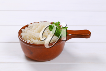 saucepan of cooked rice pasta fusilli on white wooden background