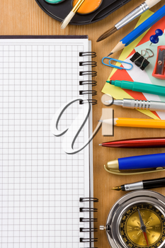 school supplies and checked notebook on wood background