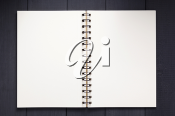 notepad or notebook paper at black wooden background surface table, top view